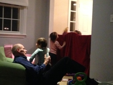 Grandpa and baby nieces watching a puppet show by other nieces...